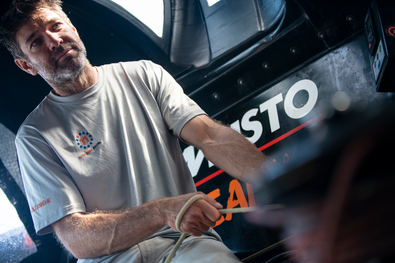 Simon Fisher of 11th Hour Racing Team in the cockpit of the team's IMOCA 60 during their August 2020 Transatlantic.