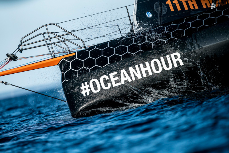 11th hour racing team IMOCA 60 bow cuts through the water with #oceanhour displayed prominently on the bow