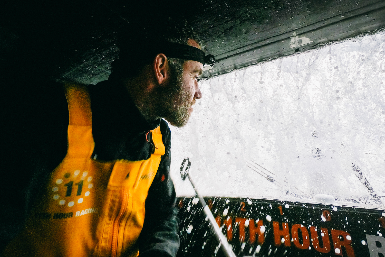 Amory Ross, OBR for 11th Hour Racing Team looking at water running over IMOCA 60 coach roof.