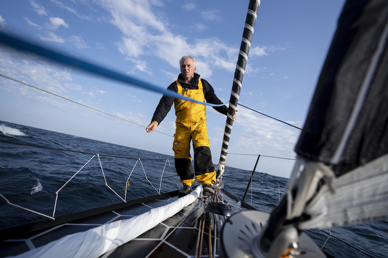 Rob Greenhalgh on the bow of the 11th Hour Racing IMOCA 60