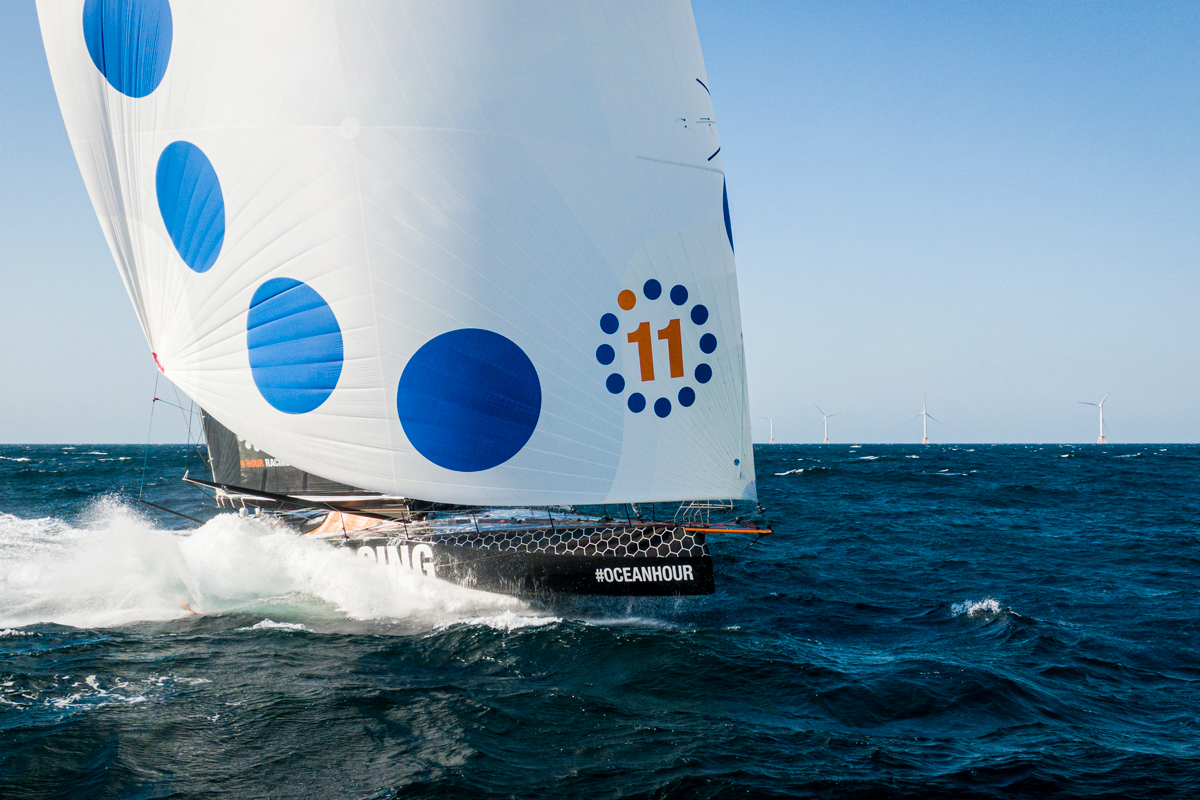 11th Hour Racing team sail past Block Island Wind Farm during an offshore training session on their IMOCA 60 as they prepare for a late-october transatlantic.
