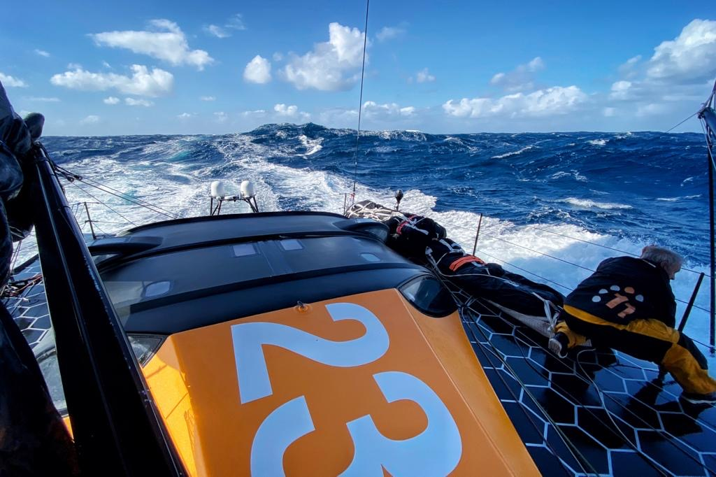 Sailor Rob Greenhalgh ties down a sail during 11th Hour Racing Team's Atlantic Crossing