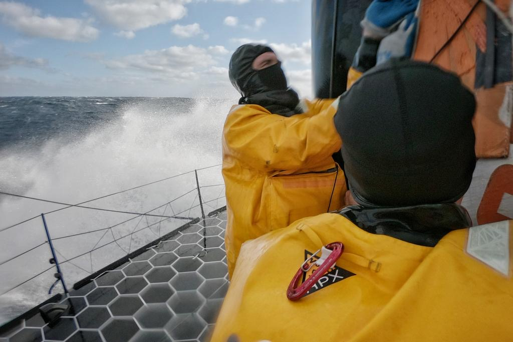 Sailors of 11th hour Racing Team on the deck of their IMOCA 60 in the Bay of Biscay on their final approach to France